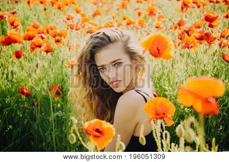 woman. girl with long curly hair hold flower in field of red poppy seed with green stem on natural background summer spring drug and love intoxication opium