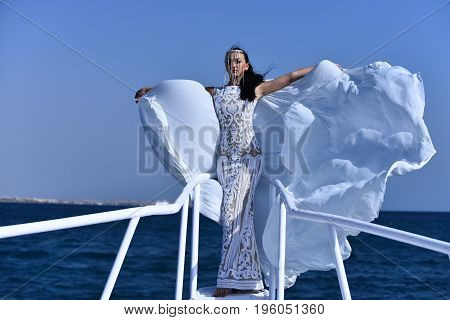 Bride woman with pretty young face in white beautiful bridal long vintage dress and fluttering wrap posing on bridge of yacht on background of blue sea and sky