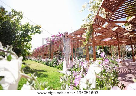 Beauty and fashion. Pretty girl or sexy woman in white dress standing on green grass in garden with blossoming flowers in resort place on sunny day on natural background. Idyllic summer vacation
