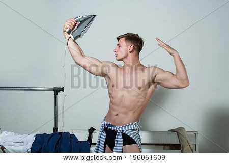 Man with muscular body hold iron. Ma