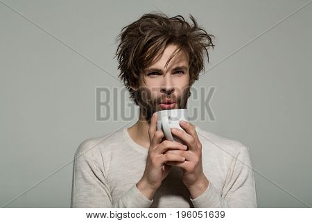 morning refreshment of man with cup of tea or coffee has uncombed hair in underwear on grey background and drink energy