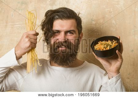 Cooking raw spaghetti in restaurant. Healthy food and dieting. Man smiling with pasta in hand. Cook or chef bearded man with bowl. Hipster hold Italian macaroni.