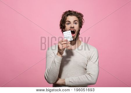 Man with pills in blister pack. Drug and antidepressant. Health and medicine. Guy hold dieting pill and vitamin. Treatment and hypnotic tablet.
