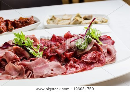 Italian Antipasto Platter Cold antipasto meat plate artichokes sundried tomato on marble surface