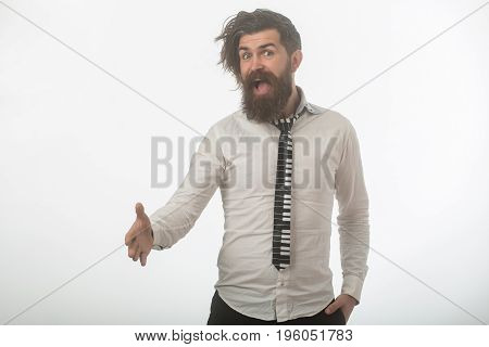 Guy hold hand for handshake. Fashion model with stylish hair isolated on white. Business fashion and beauty. Man with long beard and mustache on happy face. Hipster in shirt and musical tie.
