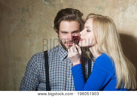 Man and girl posing with glass of red liqueur. Sexy woman with blond long hair and handsome macho on beige background. Couple in love. Alcohol and appetizer. Unhealthy lifestyle and bad habits
