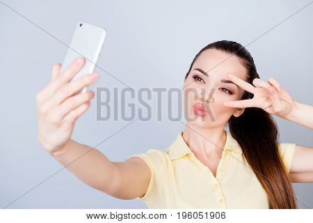 Cheers! Peace To All! Attractive Young Hispanic Teen Is Making A Selfie On The Camera And Shows Two