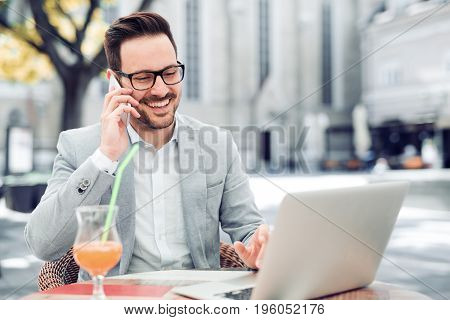 Handsome businessman talking on the phone during break in a cafe.