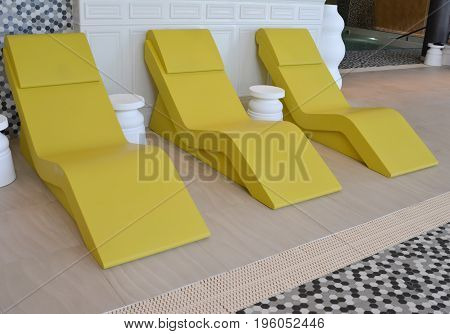 line of three yellow chaise longue in the pool