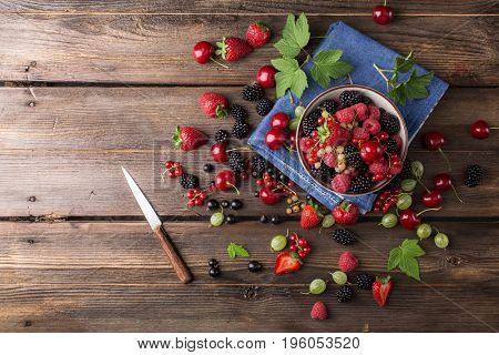 Assorted ripe berries from a garden in a bowl on a wooden board. Mix of strawberries, currants, blackberries, cherries. Top view