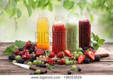 Fresh vitamin drink, colored smoothies from berries. Homemade refreshing fruit drink on a wooden board. Background of green leaves.