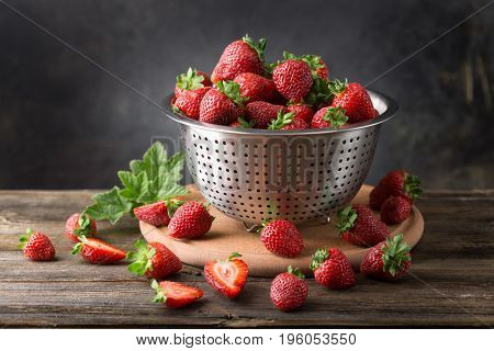 Ripe strawberry in a colander on a wooden board on a dark background