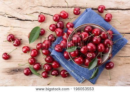 Ripe cherries in a bowl on a wooden board. Top view
