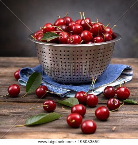 ripe cherries in a colander on a wooden board on a dark background