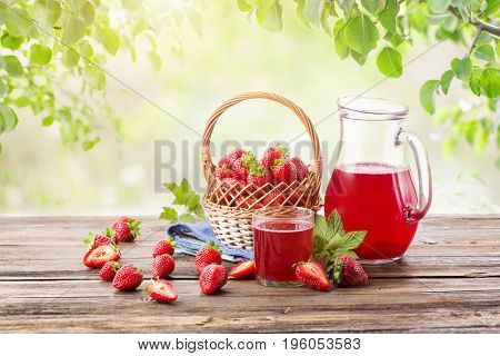 Ripe strawberry from a garden in basket and jug with homemade compote on a wooden board on a background of green leaves