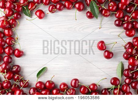 Frame of Ripe cherry from a garden with leaves on wood board. Top view