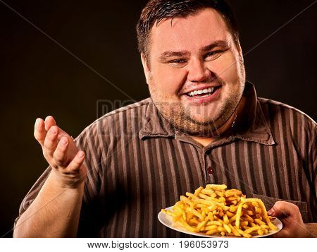 Diet failure of fat man eating fast food. Overweight person who spoiled healthy food by eating french fries. Junk meal leads to obesity. Advertising fried potatoes.
