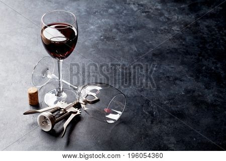 Red wine glasses and corkscrew on stone table. With copy space