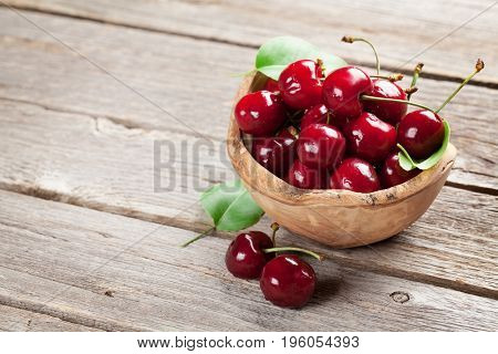 Fresh garden cherry in bowl on wooden table. With copy space