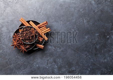 Various spices bowls over stone background. Cinnamon, anise, clove. Top view with copy space
