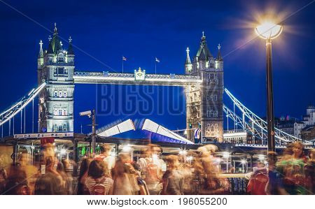 LONDON, UK - JULY 17, 2017: crowd of tourists watching Tower Bridge in the evening being raised up