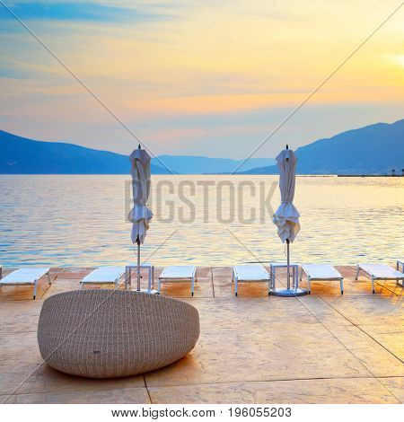 Beautiful view of sea resorts beach with chair and umberllas at sundown