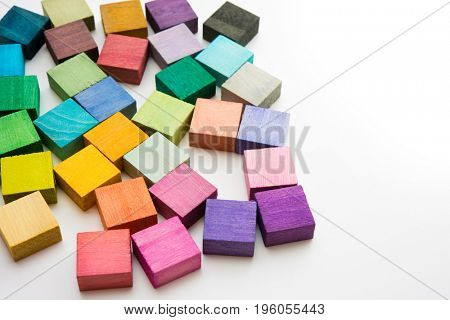 Multi colored wooden blocks on white table.  none are the same color. Background or cover for something creative or diverse.