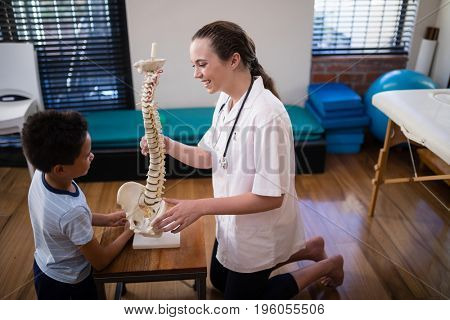 Side view of smiling female therapist explaining boy with artificial spine at hospital ward