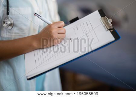 Midsection of female doctor writing on clipboard at hospital ward
