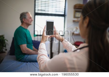 Rear view of female therapist photographing senior male patient from mobile phone against window at hospital ward