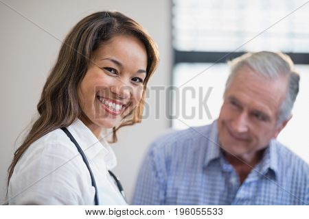 Portrait of smiling female therapist with senior male patient in background at hospital ward