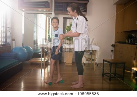 Side view of smiling boy looking at female therapist while standing on stress balls in hospital ward