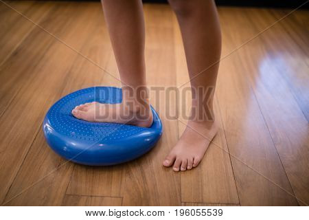 Low section of boy standing while stepping on large blue stress ball at hospital ward