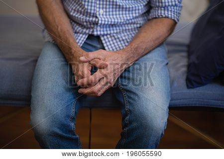 Midsection of senior male patient sitting with hands clasped on bed at hospital ward