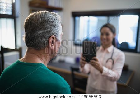 Rear view of senior male patient being photographed by female therapist at hospital ward