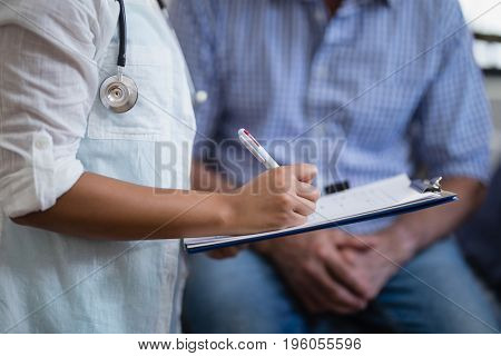 Midsection of female therapist writing on clipboard with male patient in background at hospital ward