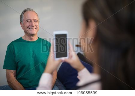 Female therapist photographing senior male patient from mobile phone at hospital ward