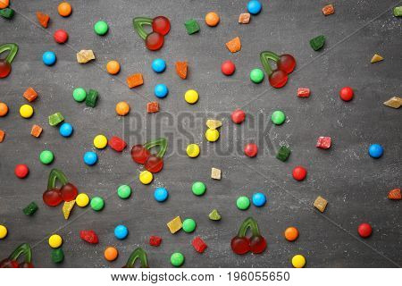 Strew of delicious candies on grey background