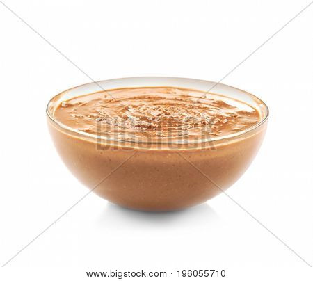 Peanut butter in glass bowl on white background