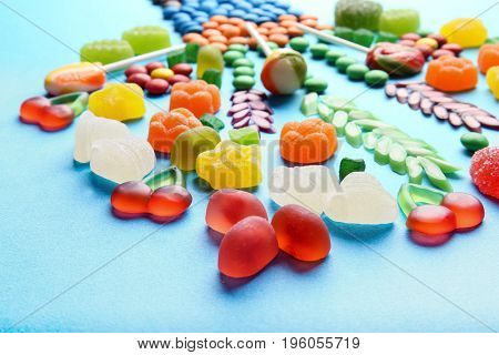 Composition of delicious candies on blue background