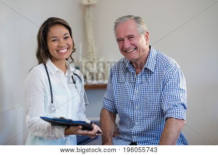 Portrait of smiling senior male patient and female therapist holding file at hospital ward