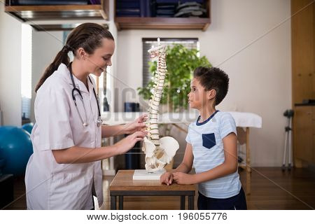 Side view of smiling young female therapist explaining to boy with artificial spine at hospital ward