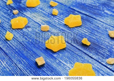 Composition of delicious star shaped jelly candies on blue wooden table