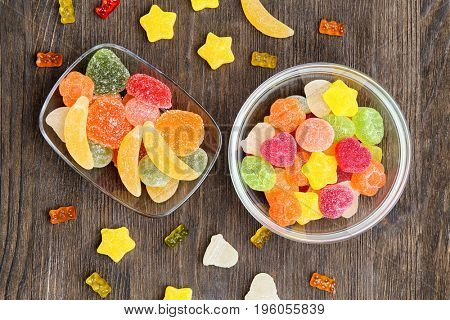 Bowls with delicious jelly candies on wooden background