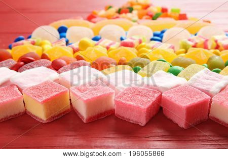 Composition of delicious candies on red wooden table