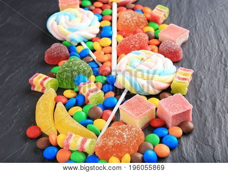 Composition of delicious candies on grey table