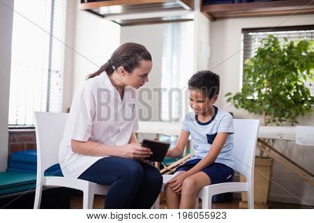 Female therapist looking at boy while using digital tablet at hospital ward