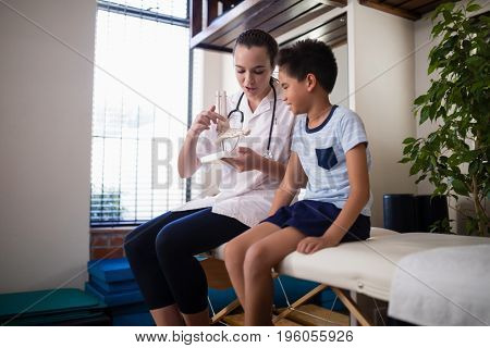 Female therapist explaining boy with artificial bone while sitting on bed at hospital ward