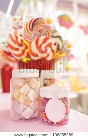 Different sweets in jars on table at candy shop