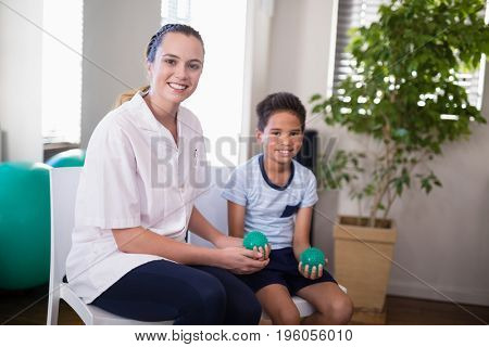 Portrait of smiling female therapist and boy holding stress balls in hospital ward